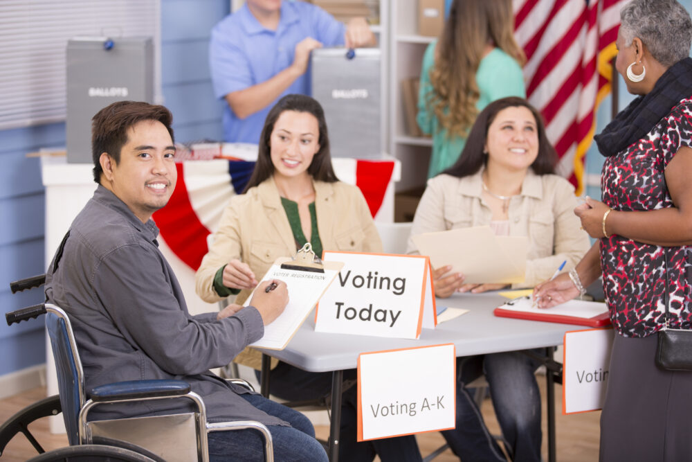 Multi-ethnic group of people registering and voting in the November USA elections at their local polling station. One disabled man in wheelchair.